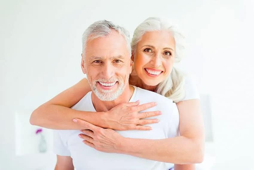 Mature couple posing for a picture, smiling