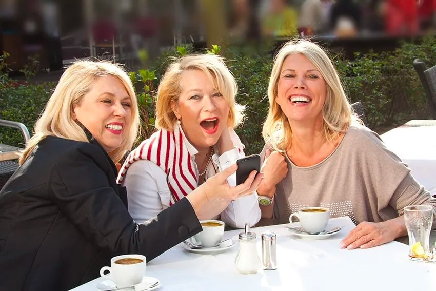 3 friends enjoy a laugh and coffee together
