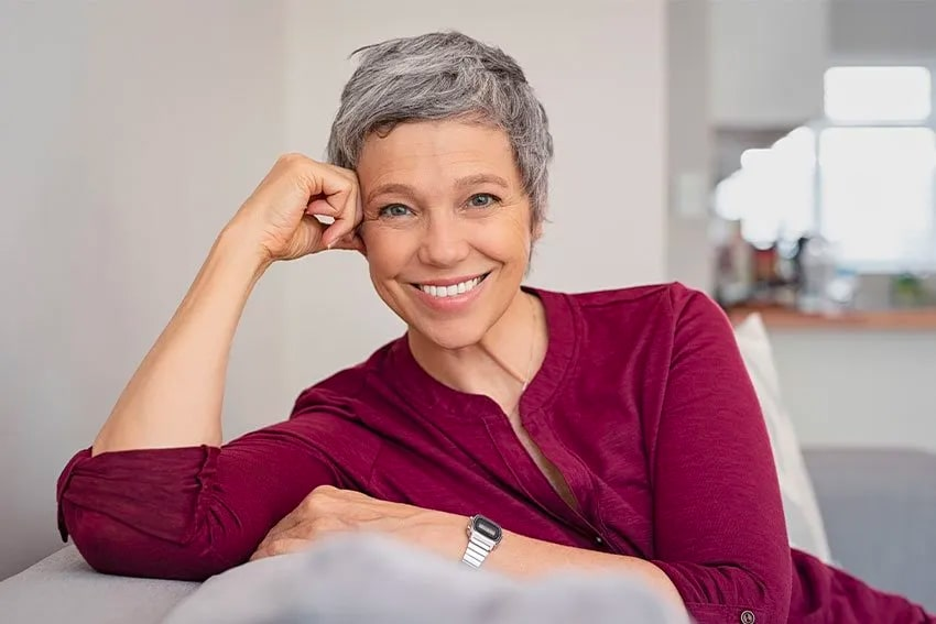 mature woman relaxing on her couch, showing off her amazing smile