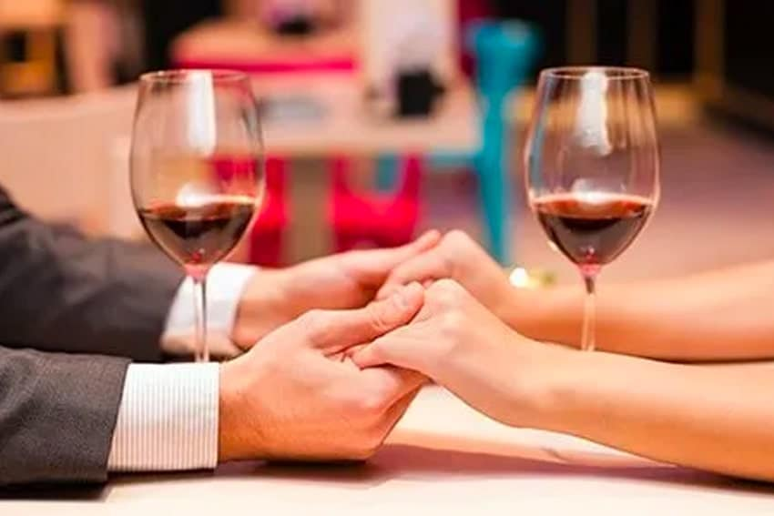 Couple holding hands over glasses of red wine