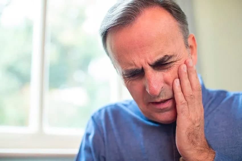 older man with a pain in his denture