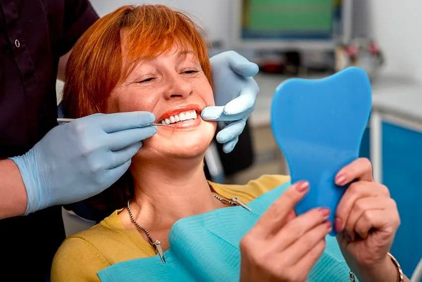 woman resting in dental chair looking at her smile