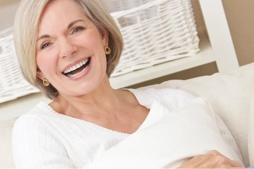 Mature woman laughing, sitting on her couch