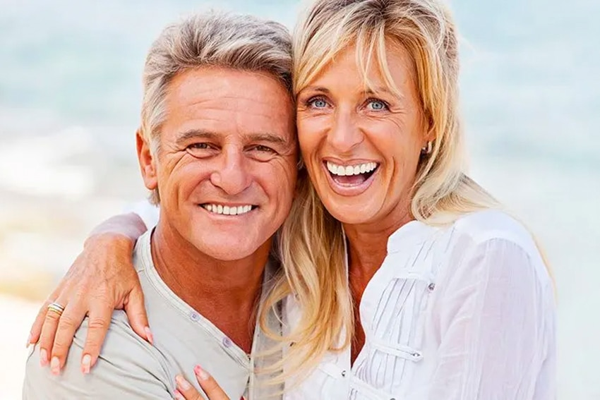 Mature couple laugh on the beach