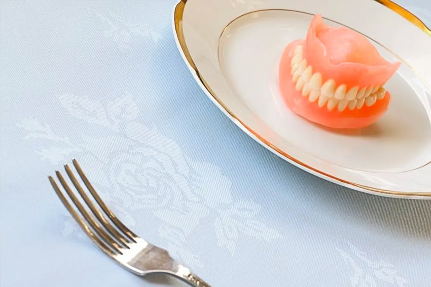 A fork sitting next to a plat with a set of dentures on it