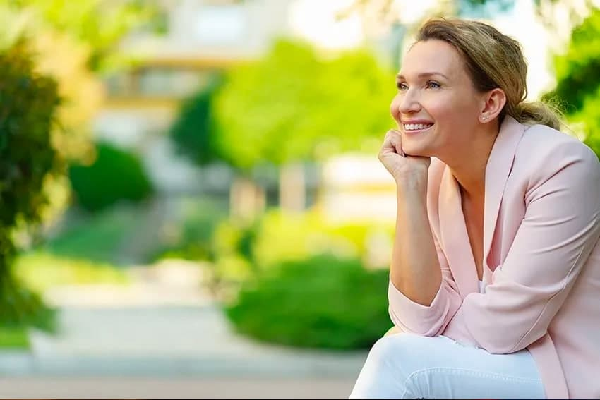 mature woman sitting on her front patio, look at the view.