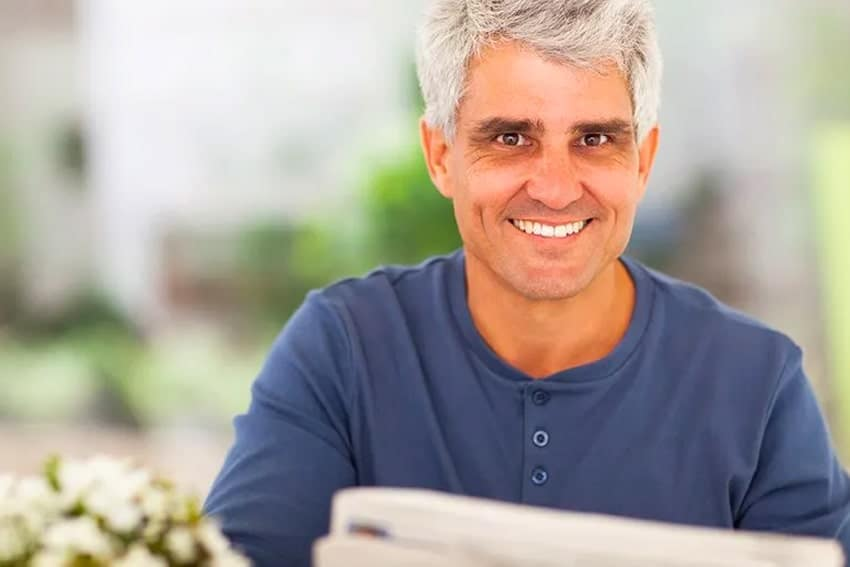 Middle aged man reading the newspaper at home
