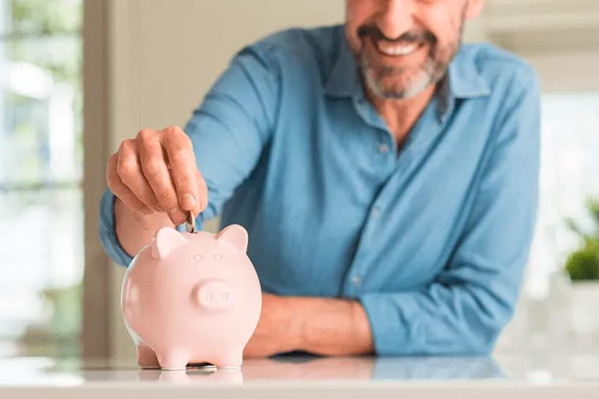 older man placing coins in a pink piggy bank