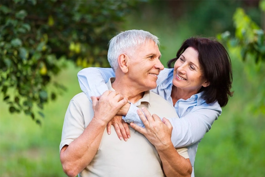senior couple outside, woman hugging husband from behind his shoulders