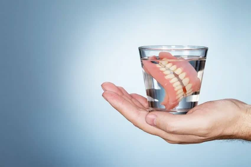 Hand holding up a glass of water with dentures soaking in it