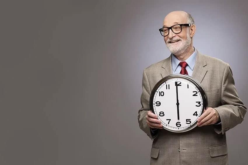 older man holding up a large clock