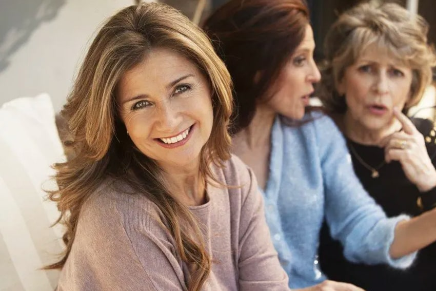 Mature woman takes a break to smile while talking with friends and family