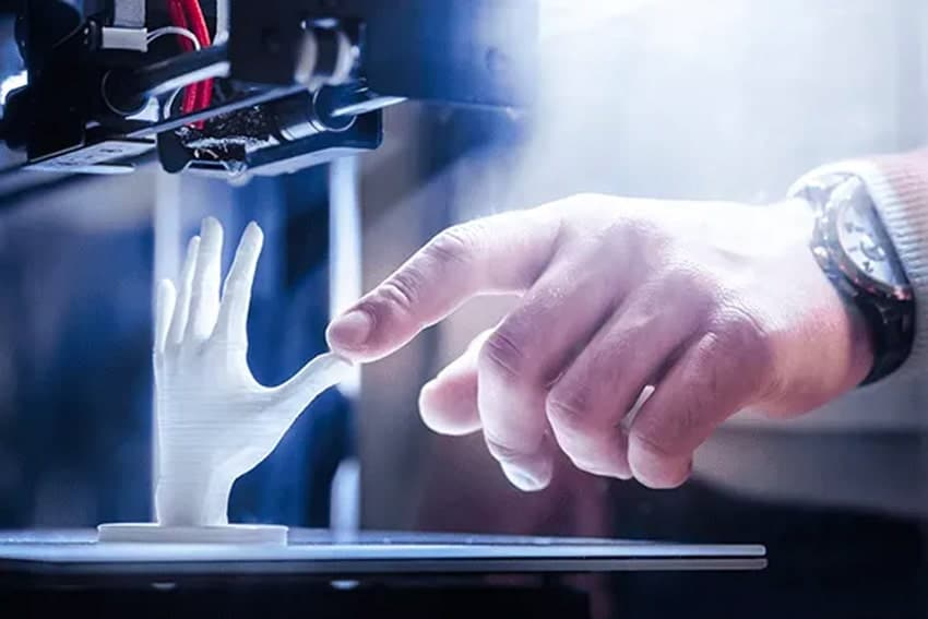 A man's hand touches a 3-d model of a smaller hand being printed