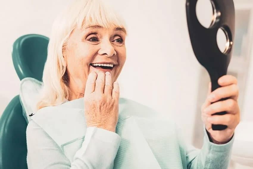 Senior woman being amazed with her new denture