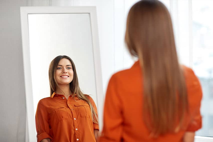 beautiful young woman looking in the mirror, smiling
