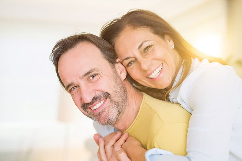 woman hugging husband around the torso from behind. Both smiling